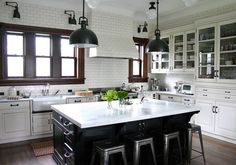 The light fixtures have a Parisian flea market look, and French café stools lend industrial style. Subway tile with gray grout is another vintage classic that blends the vent hood into the wall. Traditional hardware and wood trim finish off the look.