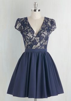 Bold, yet elegant - that's how you feel when you sport this navy dress! This frock touts a lacy overlay on its padded surplice bodice and a satiny skirt that's perfect for twirling.