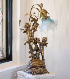 Beautiful vintage French cherub lamp with blue Venetian shade. Made of brass and sitting on an ornate brass and marble base, the lamp features two