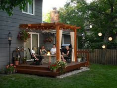 deck and pergola. Have side railings or built in seating and stairs off the front. I like the stone landing in the front. Sparking lighting is pretty. Should we have a FIRE PIT??