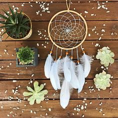 Handmade baby blue dream catcher! The hoop measures 7 inches in diameter and is covered in genuine beige suede lace. The interior is weaved with color changing blue and white thread and is decorated with clear blue beads. Wooden beads hold the fluffy baby blue feathers in place.  Perfect for