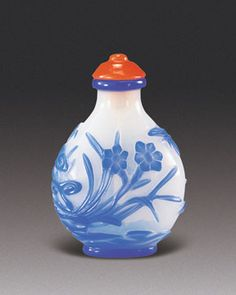 Glass snuff bottle with sapphire-blue overlay on a milky-white ground carved to illustrate a butterfly flying over a rocky ground with flowering narcissus, 1750–1790. Bloch Collection.