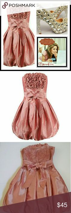 """Pink strapless dress Adorable pink strapless  dress with rosettes in the front,  gathered in the back.  Tie the bow in front or the back.  Zipper on the side,  pleated skirt,  fully lined,  polyester blend.  Length measures  25"""",  bust 28"""" laying flat. Dresses Mini"""