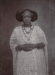 In and Out of the Studio: Photographic Portraits from West Africa. An image of a nameless woman from Senegal , taken in the 1910s, as she stares defiantly into the camera. Her hands placed gently on her stomach as if to signal she's pregnant. Her gaze is haloed by a traditional hairstyle, woven together with black wool as was the style in West Africa at the time, and punctuated by an array of carefully placed jewelry.