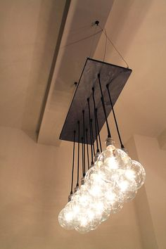 """Handmade urban chandelier. Made from reclaimed materials. Includes 15 bulbs. Wiring can be white or black (pictured). Hardware available in silver (pictured), antique gold, *copper, *antique brass, *black, or *white. Fixture can be mounted flush to ceiling or suspended down from ceiling, please let us know when purchasing.  *may involve additional costs  Dimensions: Base is 12"""" x 28"""" and bulbs hang 27"""" from base. We can customize dimensions and length of bulbs based on your needs!"""