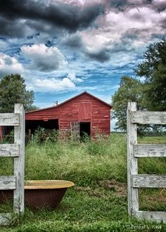 Beautiful skies in thie peaceful farmhouse scene...gates...old tub for watering livestock....