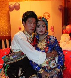 Bride and Groom from Pelyul on their wedding day, dressed in traditional ceremonial costume reserved for yearly festivals and weddings. Women's traditional headdress from Pelyul is easily recognised by lots of turqoise dressed with a single piece of amber at the crown, and often a gold bracelet worn across the forehead. The Chinese bracelets worn by the bride on each wrist may be gifts from Chinese friends. All the rest of the jewelry and clothes are Tibetan