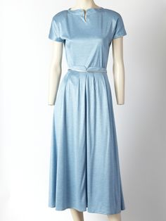 Geoffrey Beene blue jersey knit 2 piece ensemble. Top has a short sleeve with a curved neck detail. Skirt is full, high waisted with a silver band detail and an inverted pleat in the center front. Comes with matching scarf also trimmed in silver