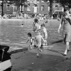 Highbury Fields Lido, Islington, London, 1964. Young woman and a small boy in a swimming costume walking along the edge of the pool with ice creams.