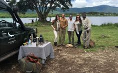 """""""Our crew (minus Robbie) with our awesome andBeyond Safari guide, Peter. Behind us is a hippopotamus watering hole."""""""