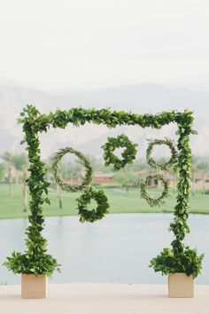 Wreath and Garland Greenery Backdrop | onelove photography | Bold Colors and Modern Sparkle in Palm Springs for a Glam Desert Wedding