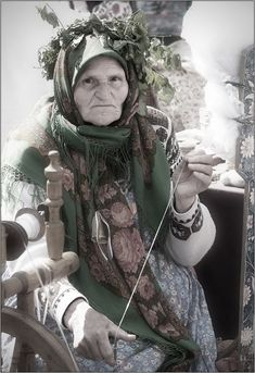 Grandmother, Sacred Spinner- She's sitting by a wheel but spinning with a handspindle that's just outside the frame at the bottom of the picture.