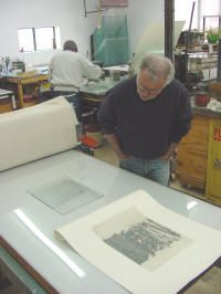 Forrest often adds a chine colle (a paper glued to another paper).  Michael has gently placed a rice paper over the inked plate.  He is dusting the paper with powered wheat paste.  Next, the plate and paper will be placed together on the press, under the larger, damp etching paper.  The final effect produces an image printed onto the rice paper (chine colle), glued down by the wheat paste, moisture, and pressure of the press.  The chine colle makes  the lightly toned area on the etching…
