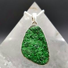 How would you like to wear the rarest garnet crystal on the planet? Uvarovite Garnet is a gorgeous druzy sparkling green crystal found in the Ural Mountains of Russia. This eye catching pendant has tiny vibrant emerald green crystals that reflect out rays of green healing energy.   Dimensions:  Crystal: 1.14 L x .79 W x .24 D 29mm x 20mm x 6mm  Length with Bail: 1.26 / 32mm  Mohs Hardness: 6.5 - 7  Chain sold separately. I have different sized sterling silver chains available. Please inquire…
