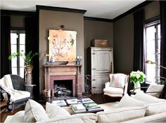 The black woodwork with the rustic, natural wood mantle and furniture is a classy take on rustic chic decor.