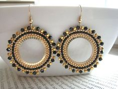 Glamour and sophistication define these stunning hoops.Handwoven with delicate japanese seed beads and Swarovsky crystals with all metal components in Black and Gold Beaded Hoops Bead Jewellery, Seed Bead Jewelry, Seed Bead Earrings, Bridal Earrings, Beaded Earrings, Jewelery, O Beads, Seed Beads, Brick Stitch Earrings