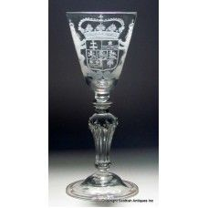 Georgian Pedestal Wine Glass Goblet which dates to 1740. It has a round funnel bowl which has been superbly engraved with a Royal Armorial with the crown above the shield supported by crowned lions either side. Sits on a really nice stem with a large angular knop at the top above an 8 sided pedestal stem which has diamonds on the shoulders. Sits upon a domed and folded foot http://www.scottishantiquesinc.co.uk/georgian-glass/newcastle-light-baluster/engraved-wine-1740#.U-3BJkjLJOE