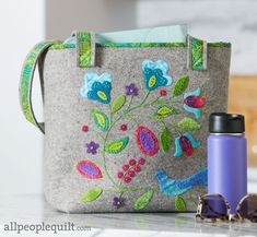 Designer Janice Joyner embellished a Wooly Felted Wonders Large Tote Kit with the Summer's Song appliqué design to create a colorful bag. Wool Embroidery, Wool Applique, American Patchwork And Quilting, Summer Songs, Michael Miller Fabric, Beaded Bags, Felt Ornaments, Applique Designs, Purses And Bags
