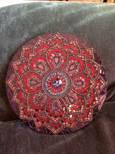 This beautiful mosaic mandala uses many brilliant colors of red, burgundy,purple and rose in an  assortment of glass, millefiori and beads.