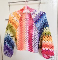 A rainbow shrug I made for myself in about 4 hours.  Simple construction, I crocheted a long rectangle so that when formed, the shrug sleeves would reach half way down my arms.  I then folded the rectangle in half, longside, and sewed each end along the longside for 16 rows.