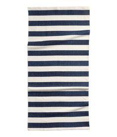Een rechthoekig vloerkleed van katoen met geprinte strepen op de bovenkant. Het kleed heeft een antisliplaag aan de onderkant.