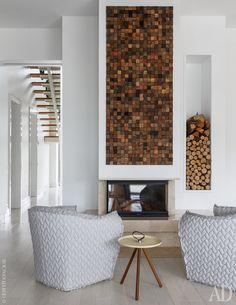 Фрагмент совмещенной гостиной-столовой-кухни на первом этаже. Возле камина обустроили небольшую лаундж-зону. Кресла Panna Chair, дизайнер Токудзин Ёсиока, Moroso.