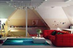 chambre sous combles avec tapis bleu, canapé rouge, table basse blanc laqué et suspensions design