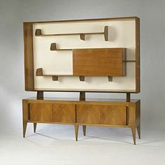 """Design Gio Ponti Launched in 1951 Manufacturer Singer & Sons Architonic id 4103501  Italian walnut, painted wood, glass, brass 79""""w x 17.5""""d x 81""""h Large scale cabinet with shelves for display and drop front door with internal glass shelves."""