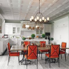 Brian J. McCarthy. Luminous Interiors. Dramatic White kitchen with gorgeous red accent kitchen chairs.