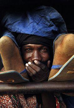 Economy Class - man between fellow passenger's feet in a truck, Niger