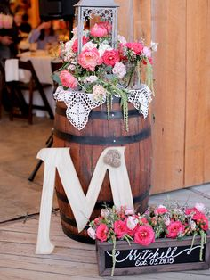 Welcome your guests to your barn wedding by fashioning rustic decor at the entrance, such as wine barrels, DIY chalk signs or fresh flower arrangements.