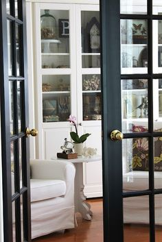 Black French doors. Love the contrast of the black doors with the white cabinets & white upholstery