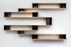 Bookcase made of 8 asymetrical wooden planks, stacked in parralel separated to each other by 11black lacquered bent steel sheet.
