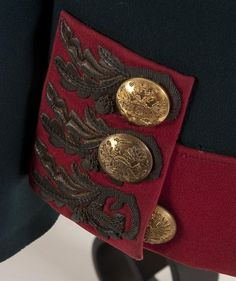 Close up view of the left side cuff and double-headed Russian imperial eagle on and Imperial Russian tunic of a senior officer of the Moscovski Guard Infantry Regiment, circa 1907. Imperial green wool double breasted tunic with red collar, cuffs and piping. Collar and cuffs richly embroidered in a gold bullion oak leaf pattern, now age darkened, unique to this regiment.