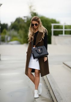 Wear a brown vest with a black long sleeved crop top, white skirt and high rise sneakers. Via Annette Haga Vest: Gestuz, Bag: YSL, Top: Bik Bok, Skirt: Vila, Sneakers: ECCO. Cute Outfits for Fall