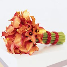 """Brides: Red Orange Calla Lily Wedding Bouquet . The bride's bouquet, made of """"Mango"""" and """"Treasure"""" calla lilies tied with a red floral sequined band trim, makes a blazing statement. Bouquet, Karen Bussen, 212-643-6880, karenbussen.com."""