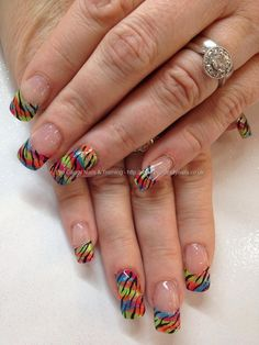 Bright multicoloured polish with black zebra nail art over acrylic nails