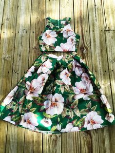 A two piece set featuring a floral print pattern all throughout. Crop top featuring a round neckline, sleeveless, zipper back closure. Skirt featuring an a-line silhouette, pleated detailing, zipper b