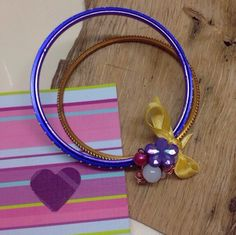 Double metal bracelet.  Purple and gold featuring yellow ribbon, beads and a purple flower.  Gift card included.  A16BAN01 by GoldRibbonsStudio on Etsy https://www.etsy.com/au/listing/289022521/double-metal-bracelet-purple-and-gold
