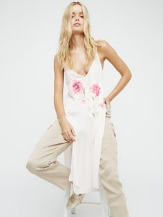 Lone Flower Maxi Top | Silky maxi top featuring a beautiful floral applique detailing on the front and back. V-neckline with crisscross straps in back and exaggerated side vents.