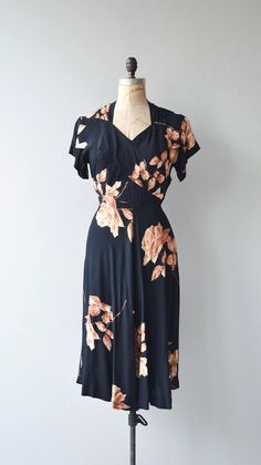 Vintage 1940s black rayon dress with coppery rose and leaf print, slight sweetheart neckline, gathered shoulders, short sleeves, cross bodice panels, fitted waist and metal side zipper. --- M E A S U R E M E N T S ---  fits like: small bust: 34-36 waist: 27 hip: 40.5 length: 44 brand/maker: n/a condition: great, some scattered pinholes small holes in the skirt, easily unnoticed when worn  to ensure a good fit, please read the sizing guide: http://www.etsy.com/shop&#x2...