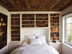 white walls, white bedding, built-in book shelves, wood planks on ceiling, artwork.