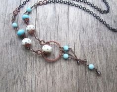 Long boho style necklace made of antiqued copper, lampwork glass*, amazonite and smoky quartz. Pendant part of the necklace is made from hand shaped copper detail and ivory white lampwork glass bead decorated with blue polka dots. Three chain dangles hang beneath, featuring lampwork glass, amazonite and quartz beads. The same materials are used to make lower part of the wire wrapped chain. The remainder of this piece of boho jewelry is comprised of antiqued copper chain. This long handmade…