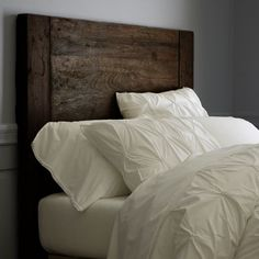I love the bold wooden headboard with the all white linens.