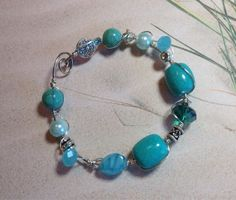 Wire wrapped glass beaded bracelet in shades of aqua blue green. Silver colored copper wire wraps through and around glass beads and finishes with