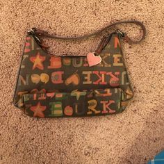 Authentic Dooney & Bourke Mini This is an authentic Dooney & Bourke mini purse, I bought this my junior year in high school, it's just sat in my closet (poor thing), it needs cleaned, does have stains on in the inside material. (Most likely ink from a pen). I loved this purse, I think I packed it nearly a year.5! It was a favorite of mine, not to big/small, for me, it was perfect. Lettering is in different colors (green, yellow, orange, & blue) the bag itself is black! Dooney & Bourke Bags…
