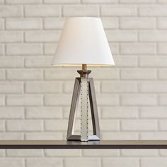 Lend a touch of industrial-chic style to your master suite or living room with this eye-catching lamp, showcasing a weathered metallic finish and tripod base.