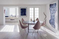 The first floor of the home features an open plan that combines the kitchen, dining room, and a small study. Drop chairs by Arne Jacobsen surround a PK58 table by Poul Kjærholm. The study includes the designer's three-legged PK11 chair alongside sculptures by artists and the couple's children.