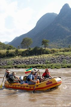 Ethiopia.Tourists whitewater rafting in river, mountains in background