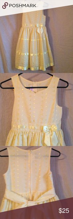 Yellow Gingham Party Dress by Ashley Ann Girls Yellow Gingham Party Dress by Ashley Ann.  Dress is 55% cotton/45% polyester. Fully lined. Lining is 65% polyester/35% cotton.  Yellow gingham material with satin ribbon accents. Back zipper closure with waist tie.  Below knee length. Dresses Formal